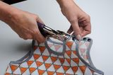 Knöpfe an den Markierungen mit Werkzeug anbringen. Alternativ kann man auch Druckknöpfe zum annähen verwenden.