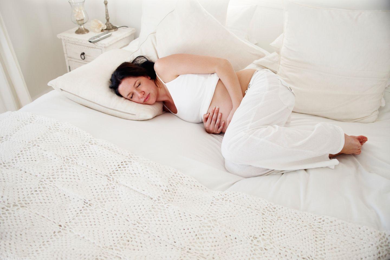 Schwangere Frau liegt mit Schmerzen auf dem Bett