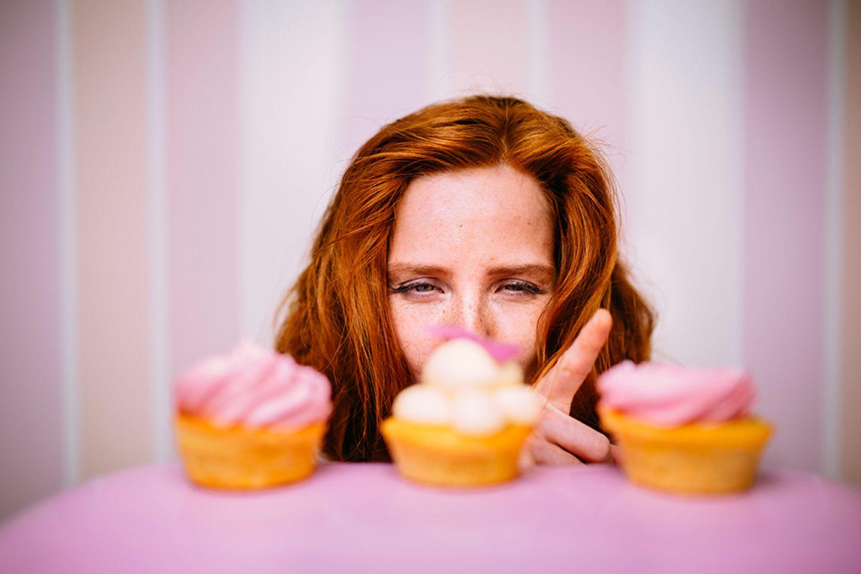 Frau will leckere Cupcakes essen