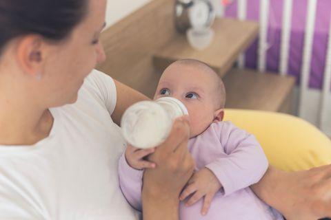 Mutter gibt Baby die Flasche