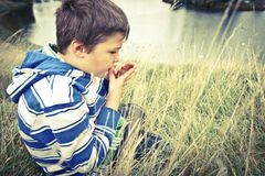 Junge pfeift auf Grashalm