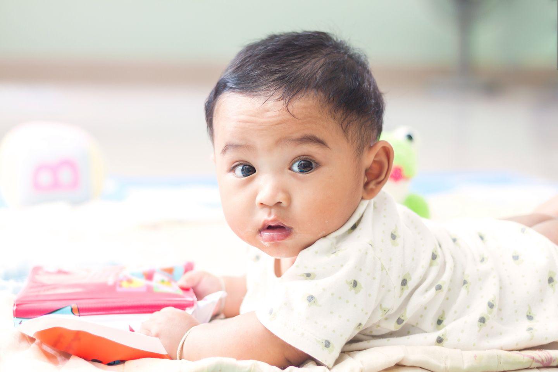 Baby stützt sich auf den Armen an