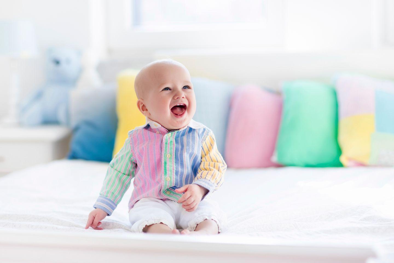 Baby sitzt und lacht