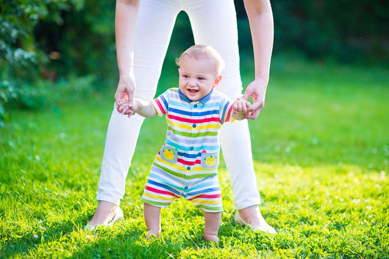 Baby läuft an der Hand