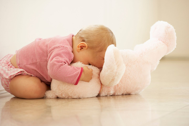 Baby spielt mit Teddy