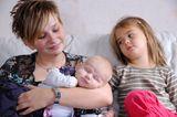 Mutter mit Baby und trauriger Schwester