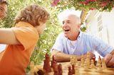 Großvater und Enkel spielen Schach