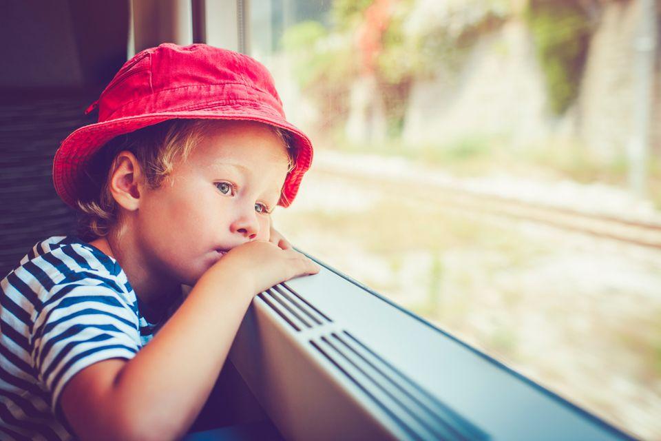 Kind schaut im Zug aus dem Fenster