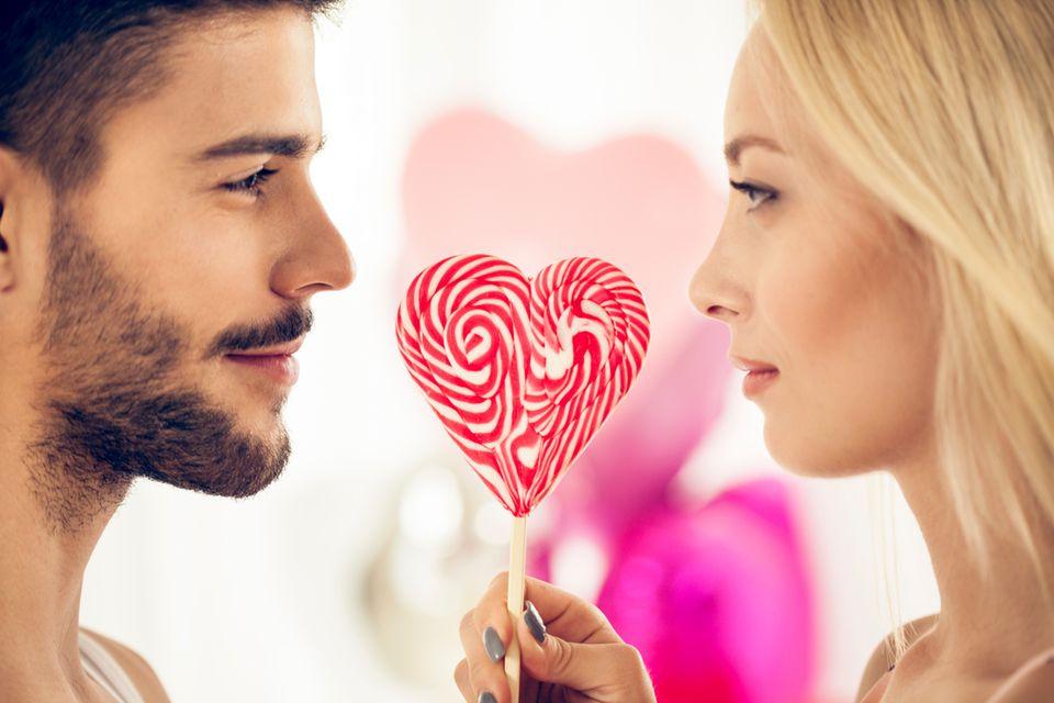 Man und Frau mit herzförmigem Lolli