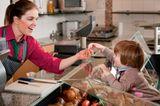 Kind bekommt im Supermarkt ein Würstchen