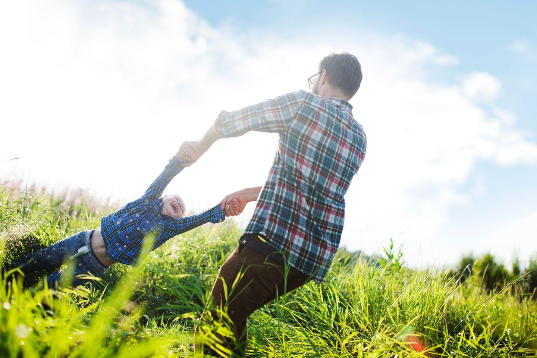 Vater wirbelt Kind durch die Luft