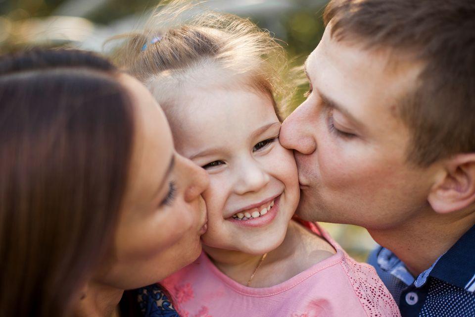 Eltern küssen ihre Tochter