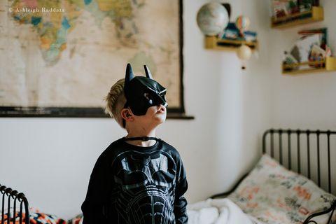 Junge im Batman-Kostüm auf seinem Bett