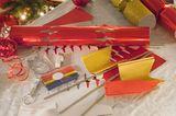 Knallbonbons bringen Party-Stimmung auf den gedeckten Tisch und versprechen Spaß für die Kids. Ihr könnt sie gemeinsam am Silvestertag selbst basteln. So sind die Kinder beschäftigt und die Vorfreude steigt.   Ihr braucht dazu nur:     ein paar leere Toilettenpapierrollen  Seidenpapier  Geschenkbänder oder Schnüre  Geschenkpapier  Tesa  Süßigkeiten zum Füllen    Und so gehts:   Die Toilettenpapierrolle mit Süßigkeiten oder anderen kleinen Überraschungen füllen. Nun die gefüllten Rollen mit buntem Seidenpapier umwickeln. Die Seiten jeweils offen lassen. Zuguterletzt das Bonbon basteln: Geschenkpapier (circa zehn Zentimeter länger als Toilettenpapierrolle) einmal um die gefüllten und in Seidenpapier gewickelten Rollen legen und mit Tesa befästigen. Die überstehenden Papierenden mit Geschenkband oder -schnur abschnüren. Fertig ist das Knallbonbon. Tipp: Je dünner das Geschenkpapier ist, desto leichter lassen sich die Bonbons beim gemeinsamen Ziehen öffnen.