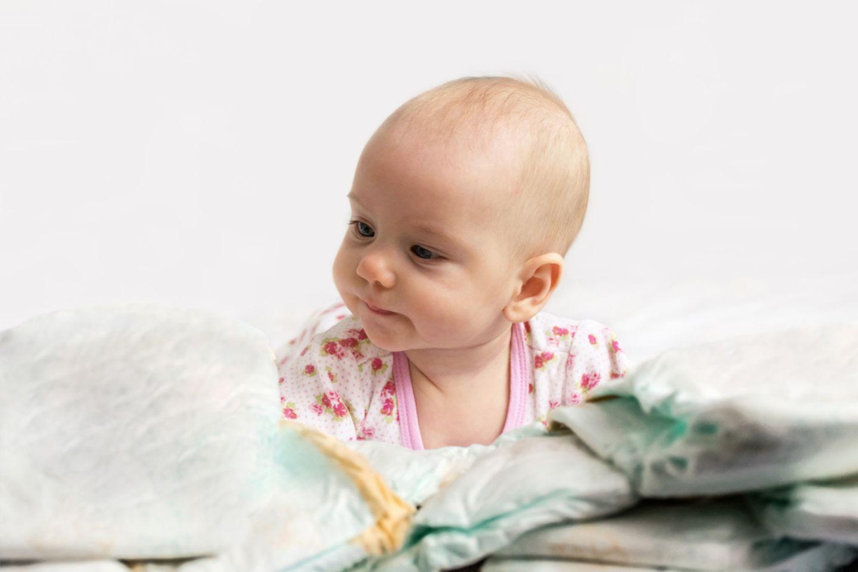 Baby mit einem Stapel Windeln
