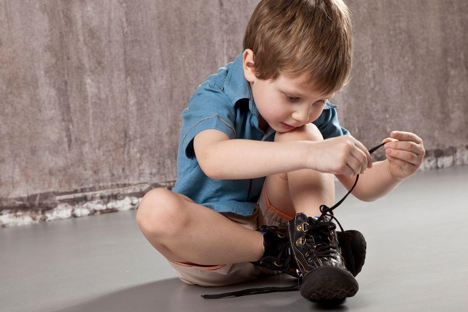 Junge bindet eine Schleife