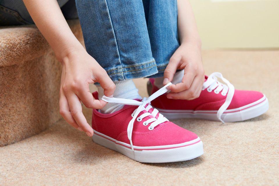 Mädchen bindet sich den Schuh zu