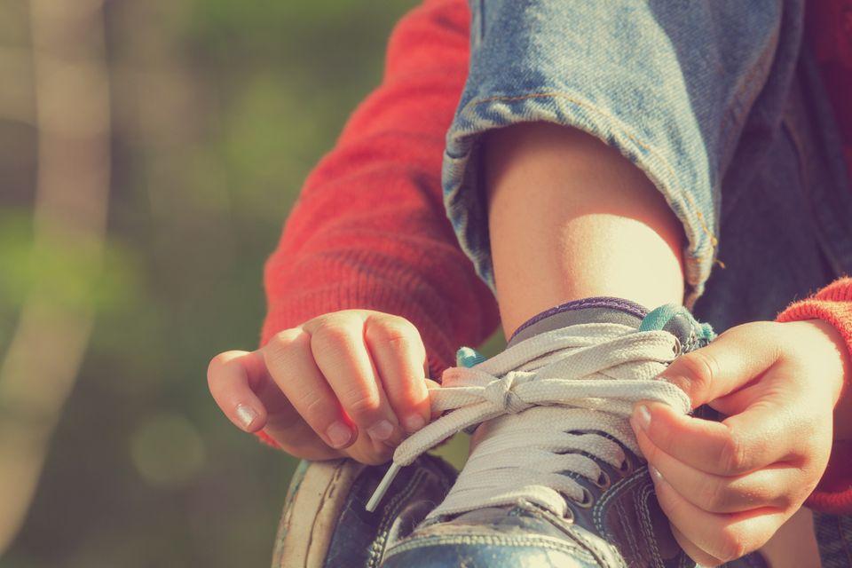Kind bindet seinen Schuh zu