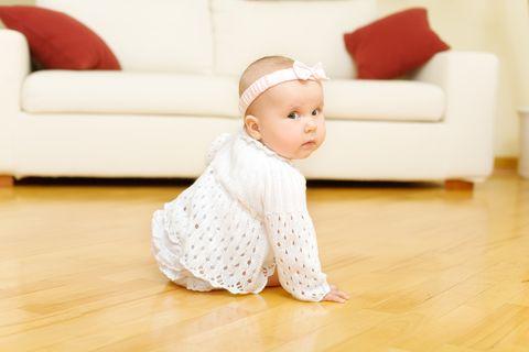 Baby sitzt und dreht den Kopf