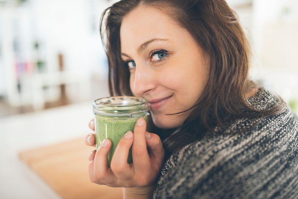 Frau mit grünem Smoothie in der Hand