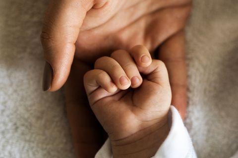 Mutter hält die Hand ihres Kindes.