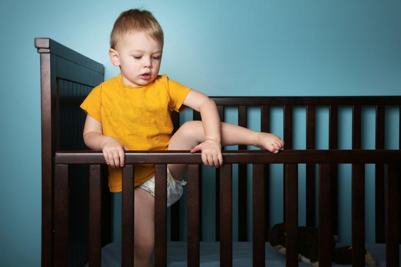 Kleinkind klettert aus dem Babybett