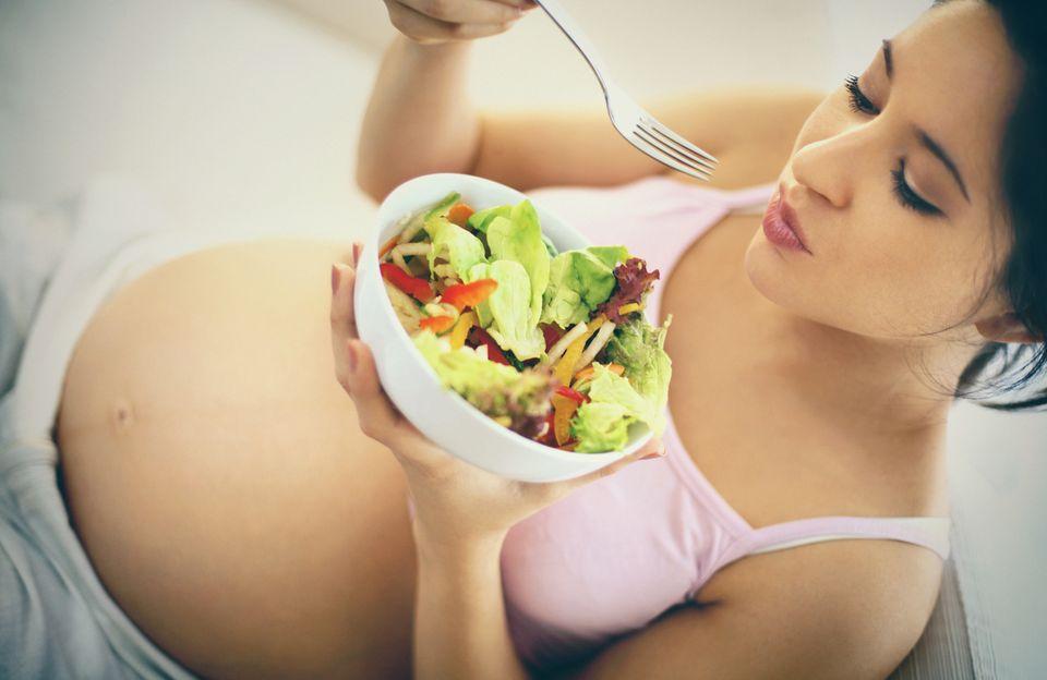 Schwangere Frau isst ein Salat