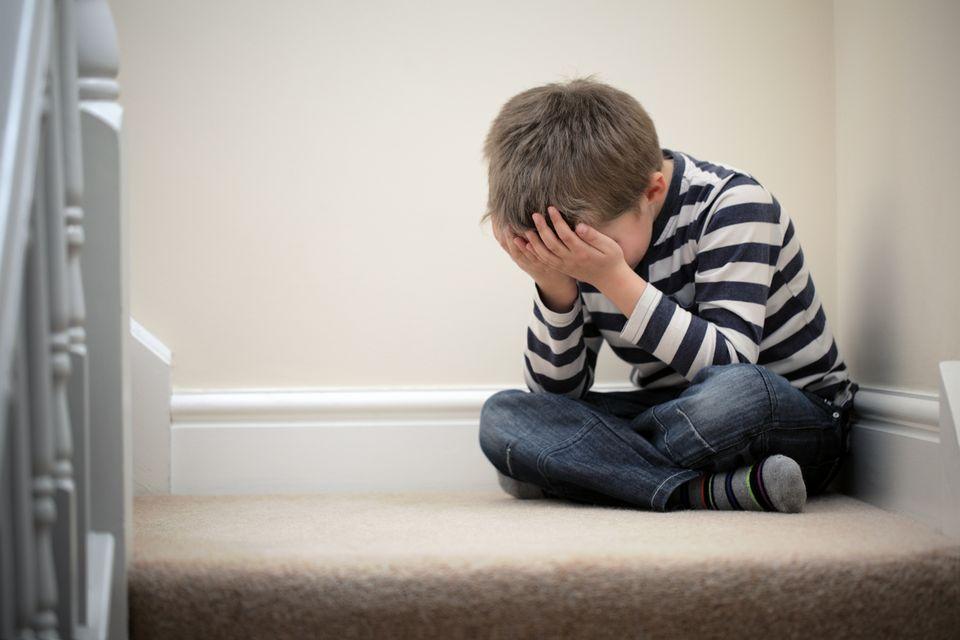 Junge sitzt zur Strafe auf der Treppe