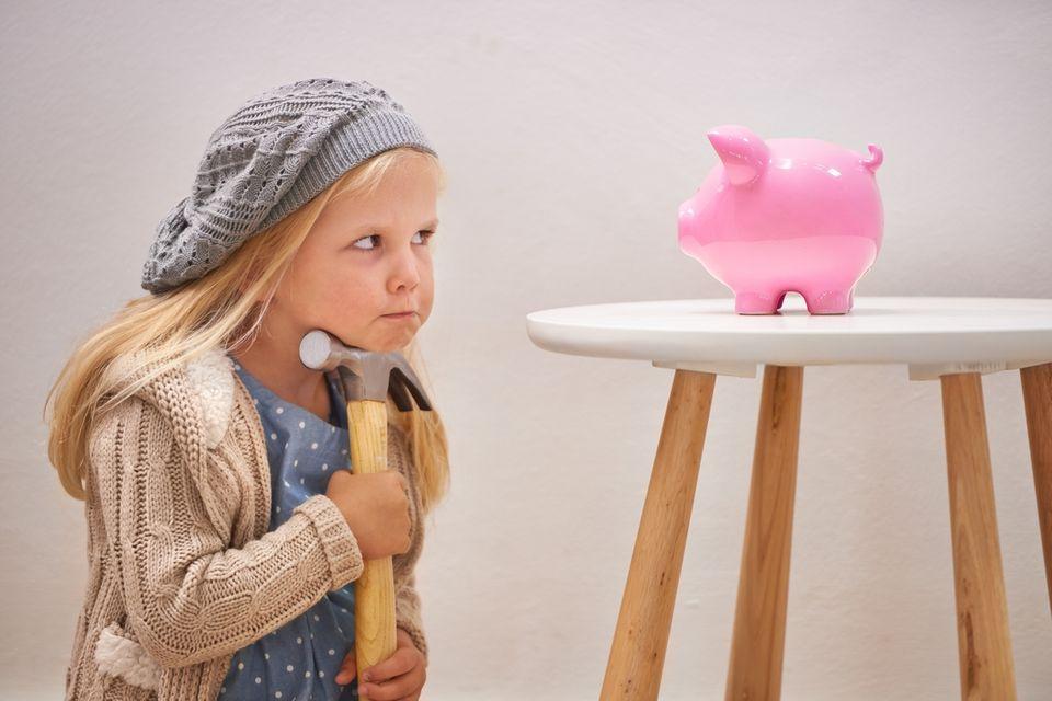 Mädchen überlegt, soll ich mein Sparschwein schlachten?