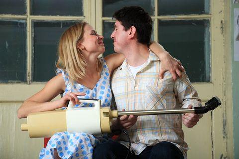 Mann und Frau flirten mit dem Staubsauger