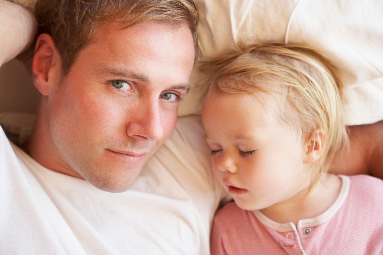 Vater bringt kleine Tochter zu Bett