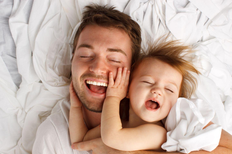 Papa macht mit Kind Quatsch im Bett