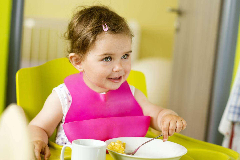 Kleines Mädchen beim Brei essen
