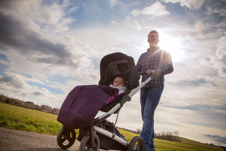 Vater beim Spazierengehen mit Kinderwagen