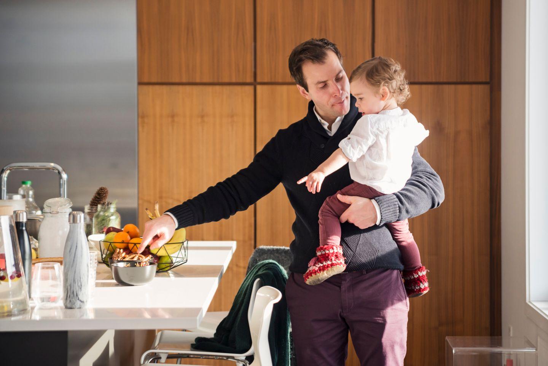 Vater hat kleine Tochter auf dem Arm in der Küche