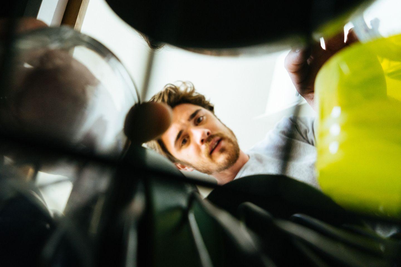 Mann räumt Geschirrspüler aus