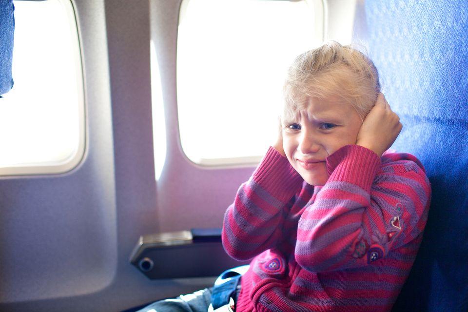 Mädchen hält sich die Ohren zu im Flugzeug