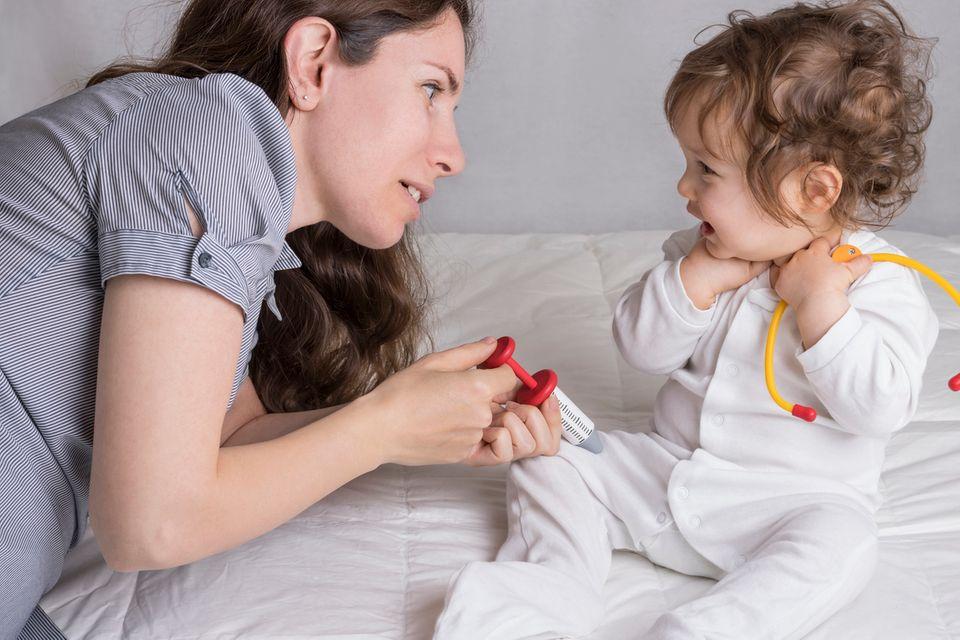 Frau und Kind spielen Impfen