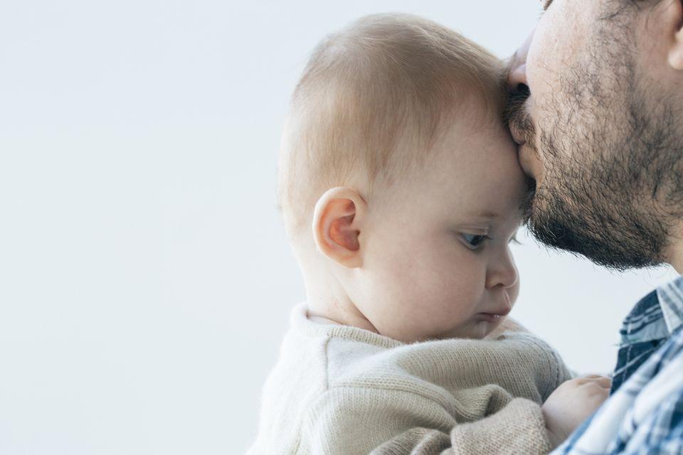 Vater küsst Baby auf die Stirn