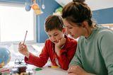 Mama und Kind lernen am Schreibtisch