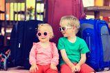 Kinder auf Koffern