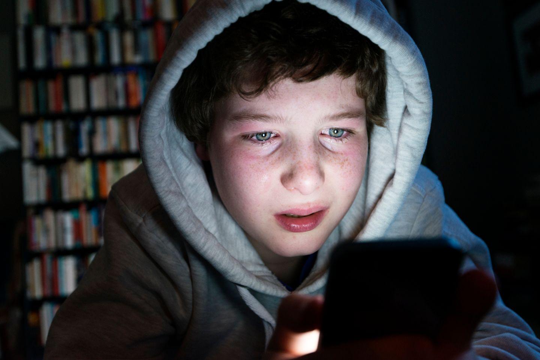 Junge weinend am Smartphone