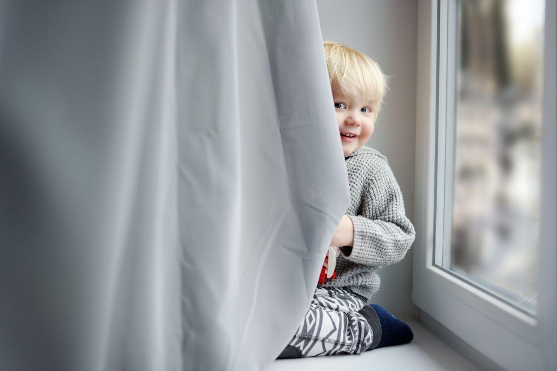 zweijähriger Junge sitzt auf Fensterbank