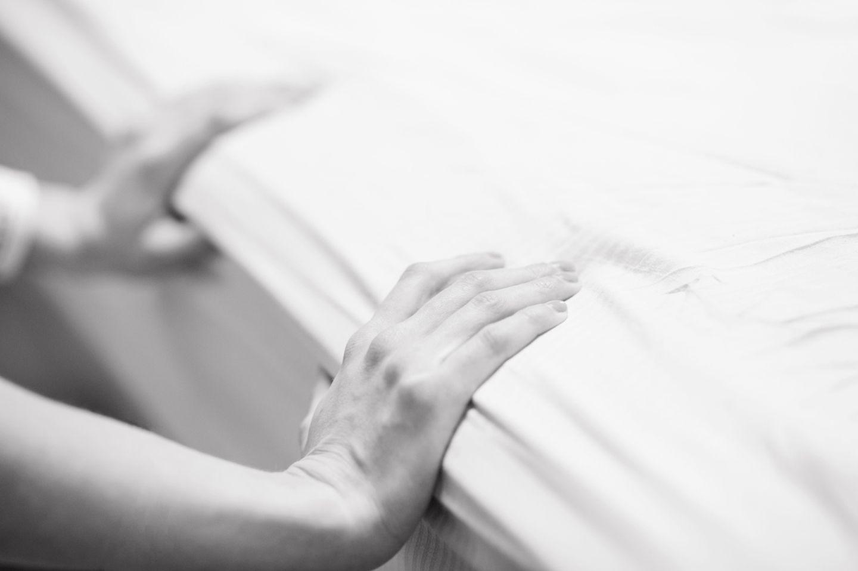 Frau unter Wehen stützt sich am Bett ab