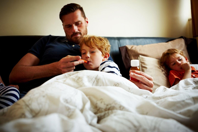 Vater mit kranken Kindern im Bett