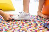 Durch Drücken auf die Schuhspitze, die so genannte Daumenprobe, kannst du prüfen, ob der Daumen zwischen den längsten Zeh und die Schuhspitze passt. Dabei sollte dein Kind stehen. Wenn ja, verfügt der Fuß über ausreichend Freiraum und der Schuh ist lang genug. Allerdings ist diese Messmethode nur ein sehr grober Anhaltspunkt, ob der Schuh passt oder nicht. Kinder ziehen bei einem Daumendruck reflexartig die Zehen ein, sodass der Schuh größer wirkt.