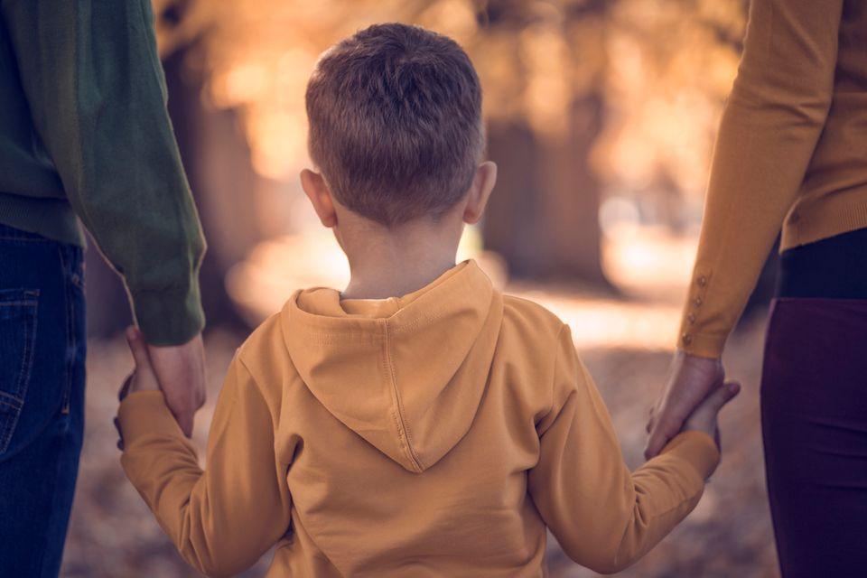 Kind geht an der Hand seiner Eltern