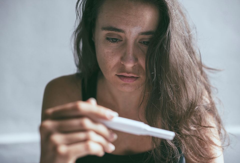 Unglückliche Frau mit Schwangerschaftstest