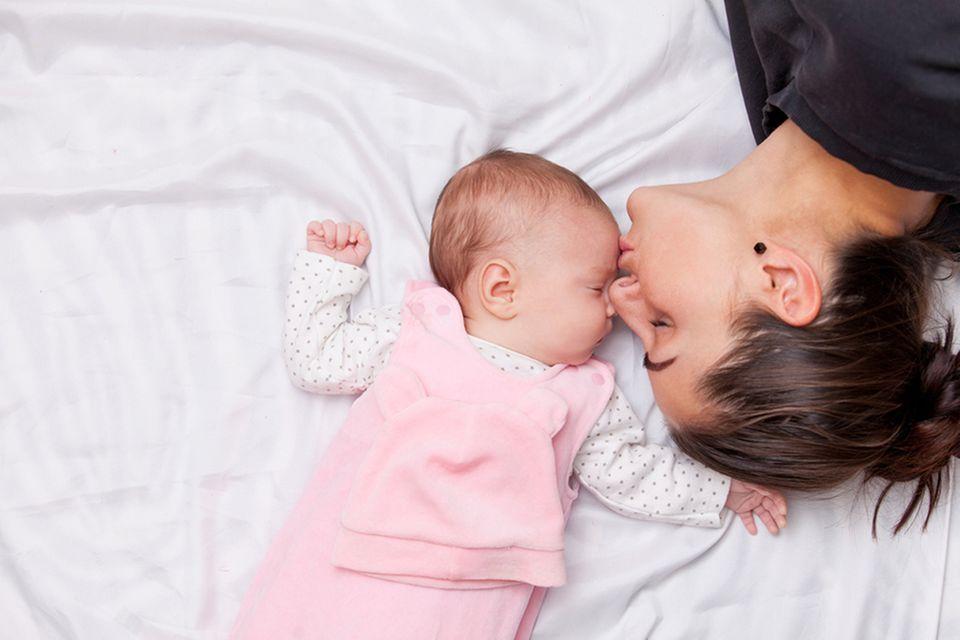 Baby wird von Mutter auf die Stirn geküsst