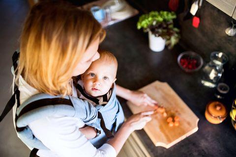 Mutter kocht mit Baby auf dem Arm